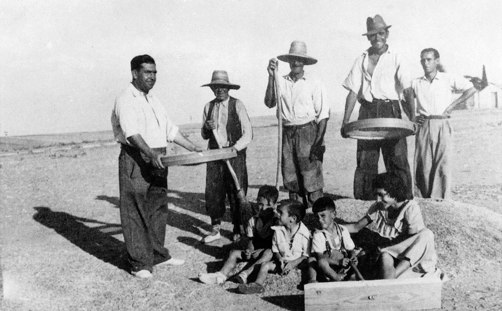 Antonio García (izquierda) con trabajadores desgranando el trigo en las eras de su propiedad.