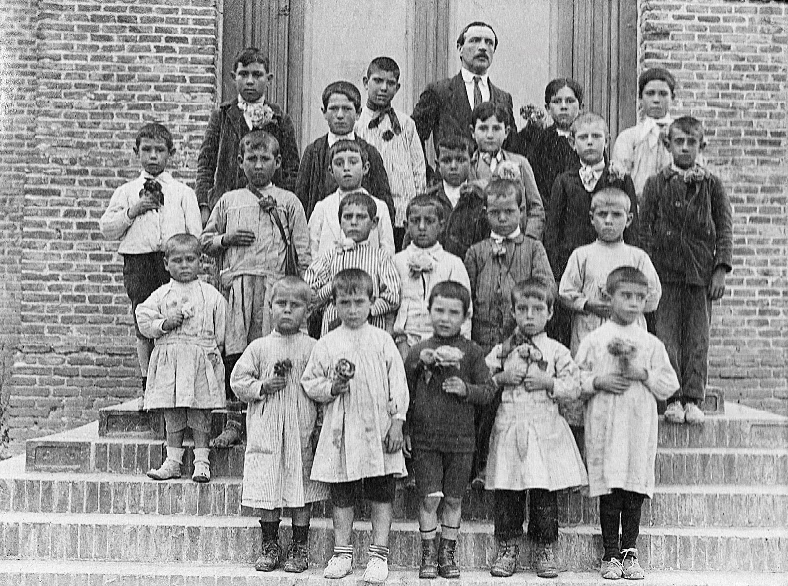 Grupo escolar con su maestro posando en la escuela pública y portando flores en la primera década del siglo XX.