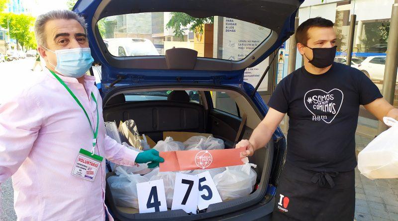 Alonso de la Plataforma de Trabajadores en Paro y Jaime propietario del local preparan el coche para el reparto